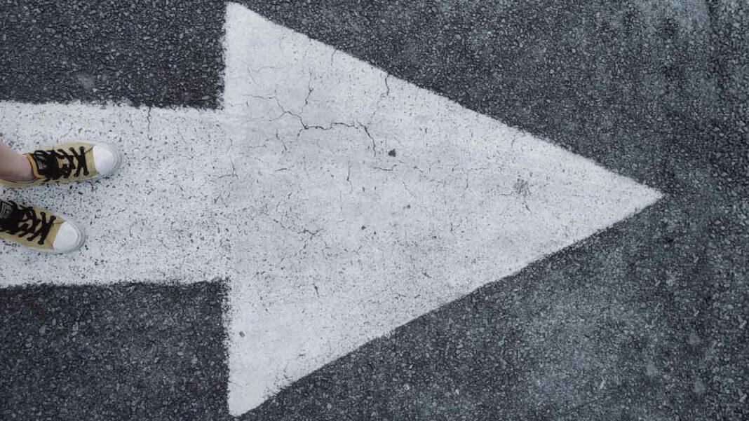 pessoa parada frente a grande seta no chão que representa o caminho a seguir e as resoluções de ano novo