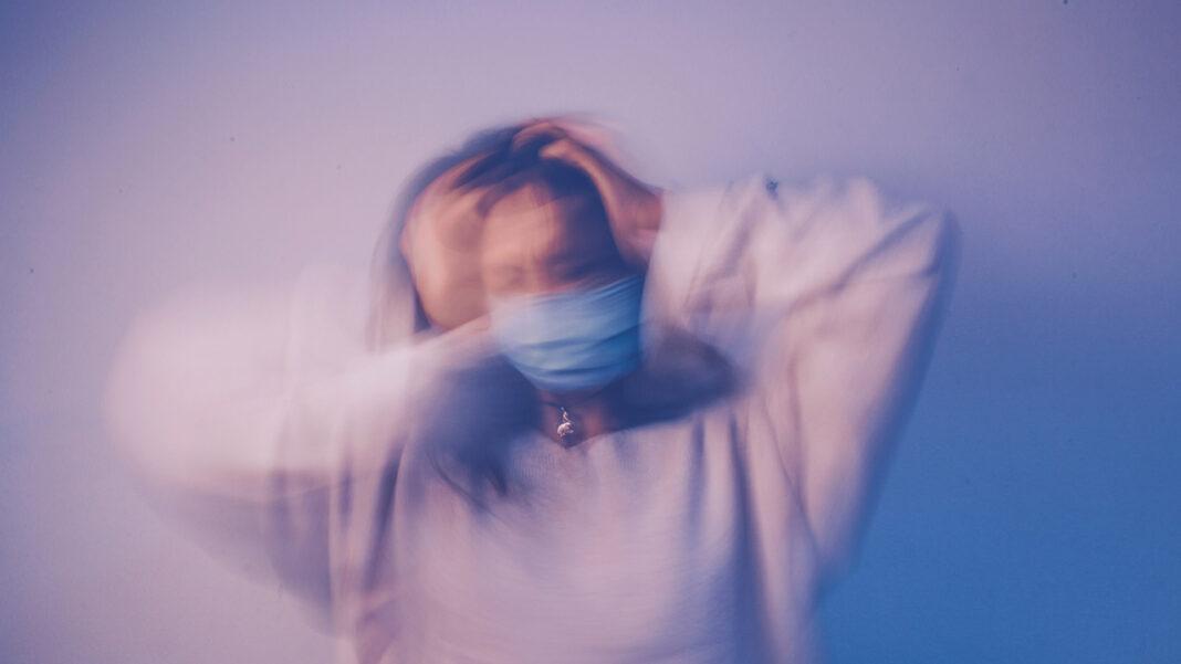 pessoa com m´+ascara, desfocada e confusa sem conseguir comunicar
