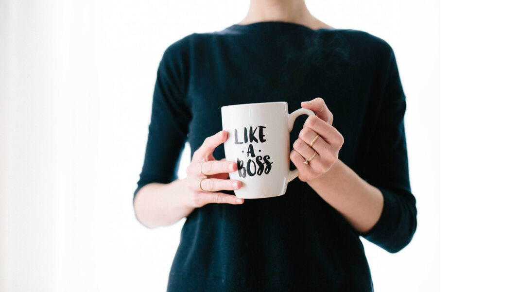 Mulher a segurar caneca com a frase «like a boss» para simbolixar um vendedor extraordinário