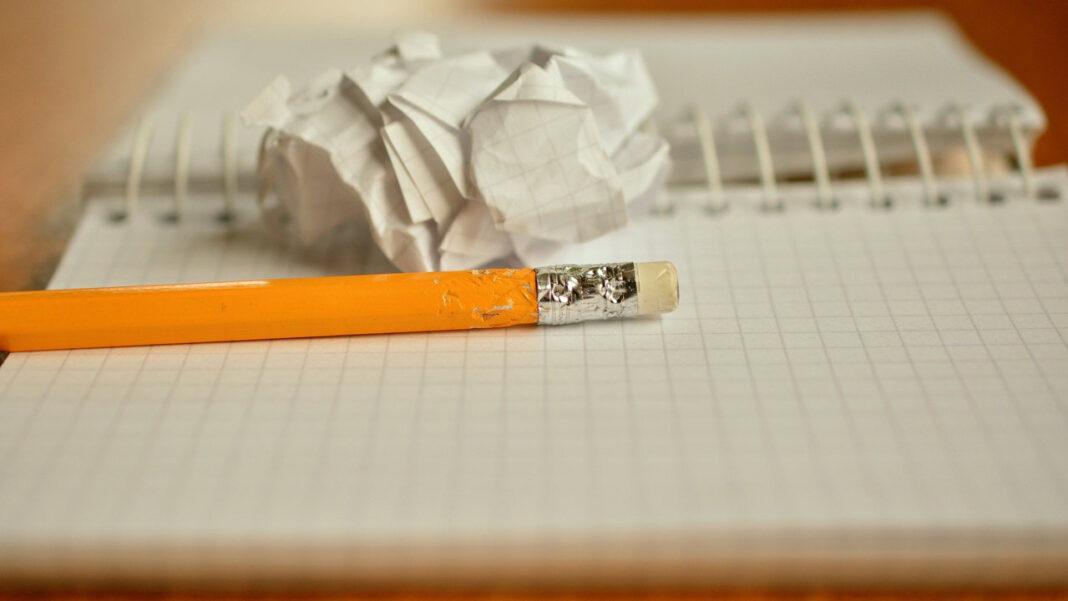 Lápis com ponta roída e folha de papel amuchacada em cima de um caderno quadriculado com as folhas em branco, a simbolizar os erros de copywriting num website
