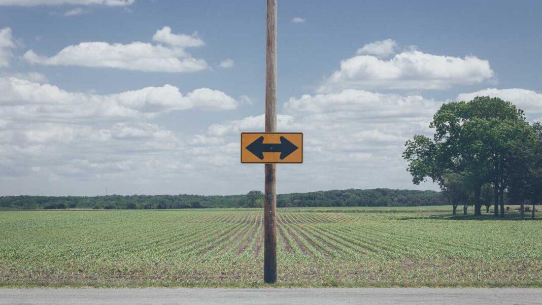 Poste de madeira num campo com 2 setas a apontar para direções opostas a simbolizar a escolha do que fazer com o marketing digital do seu negócio